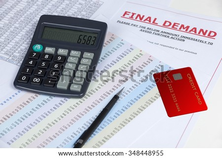 Final demand letter on a desk with a credit card and a calculator and some statements - stock photo