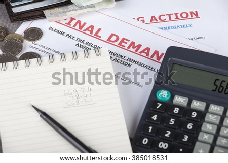 Final demands on a table with some cash in a wallet with a calculator
