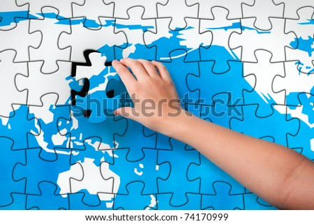 Final Piece. Child's hand, inserting missing piece of jigsaw puzzle into the world map hole. Photomontage, combined from photography and 3D-rendered image - stock photo