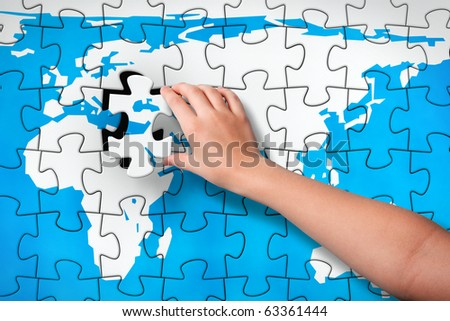 Final Piece. Child's hand, inserting missing piece of jigsaw puzzle world map into the hole. Photomontage, compiled from photography and 3D-rendered image - stock photo