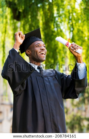 Finally graduated! Happy young African man in graduation gowns holding diploma and rising arms up  - stock photo