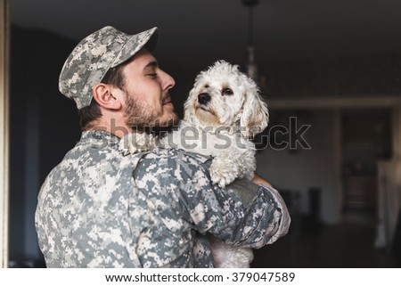 Finally home. I missed you like crazy. Soldier hugging his dog. Depth of field, selective focus - stock photo