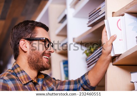 Finally I found this book. Happy young man choosing book from bookshelf and smiling while standing in library - stock photo