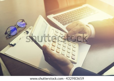 finance,accounting,business man accountant or banker making calculations.Savings,finances and economy with calculator,Man Analysis Accounting,money concept ,vintage color,selective focus - stock photo