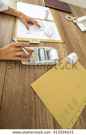 Finance and accounting concept - closeup of office desk with paperwork, documents and data and female hands using calculator and holding printout receipt. - stock photo