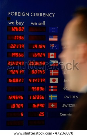 Finance and business image of a man rushing past a currency board - stock photo