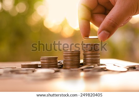 Finance and Money concept,Hope of investor concept,Male hand putting money coin like stack growing business