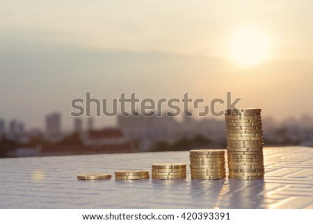 Finance and Money concept, Money coin stack growing graph with sunlight, sunset, sunrise background. - stock photo