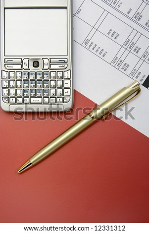 finance balance with  gold pen  and mobile