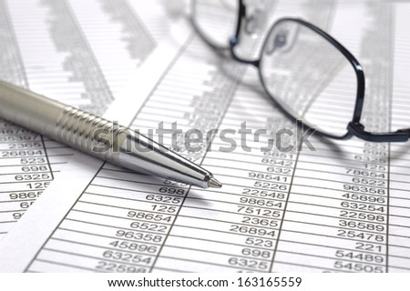 finance business calculation with glasses, chart and pen - stock photo