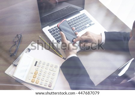 Finance & Business,Man sitting on table andusing mobile smart phone typing message on phone,financial manager taking notes  in office,selective focus,vintage tone - stock photo
