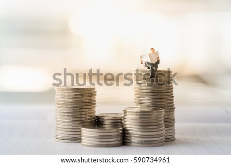 Finance, Business, saving concept. Close up of businessman miniature figure toy sit and read newspaper on stack of coins
