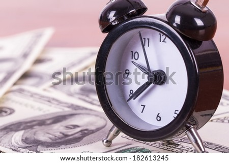 Finance concept, alarm clock and one hundred dollar banknotes on wooden table. - stock photo