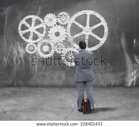 Finance concept. Businessman looking gears on chalkboard - stock photo