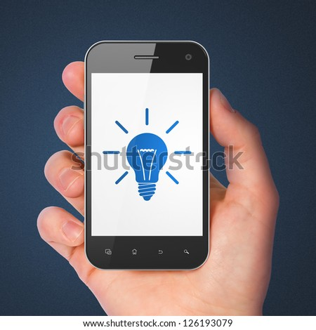 Finance concept: hand holding smartphone with Light Bulb on display. Generic mobile smart phone in hand on Dark Blue background. - stock photo
