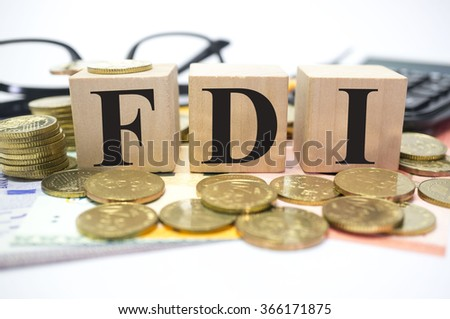Finance Concept with Stack of Coins, FDI or Foreign Direct Investment written