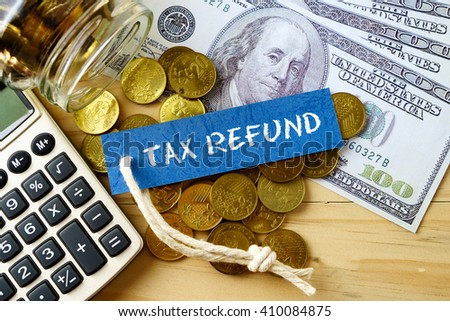 Finance conceptual image with TAX REFUND words, hundred dollar bills, golden coins and calculator on wooden background. - stock photo