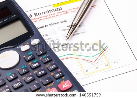 Finance report sheet with calculator and metal pen