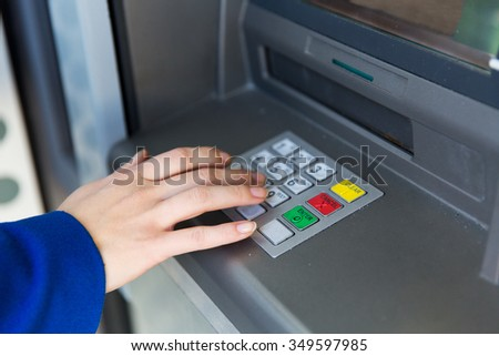 finance, technology, money and people concept - close up of hand entering pin code at cash machine - stock photo
