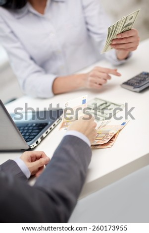 finances, currency, exchange rate, technology and people concept - close up of hands counting dollar and euro money with calculator - stock photo