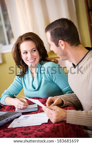 Finances: Smiling Woman and Man Working On Finances - stock photo