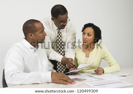 Financial adviser explaining plans to couple in office