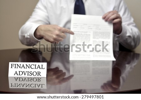 Financial advisor sitting at desk holding document up for investor investing - stock photo