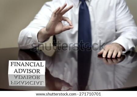 Financial advisor sitting at desk holding OK sign on hand to show good plan - stock photo