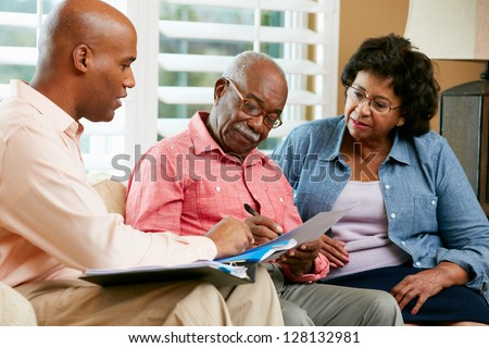 Financial Advisor Talking To Senior Couple At Home - stock photo