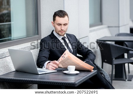 Financial affairs. Successful and confident businessman sitting at the table drinking coffee and reading a financial newspaper. Young man in formal clothes working on a laptop