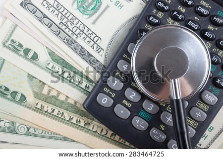 Financial analysis, audit or accounting - Stethoscope over a calculator and dollar bills. Medical costs, financial concept - stock photo