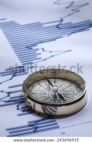 financial analysis/Close-up of a compass on stock market data chart  - stock photo