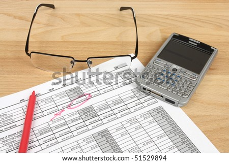 Financial analysis - income statement, red pen, glasses and a smart phone - stock photo