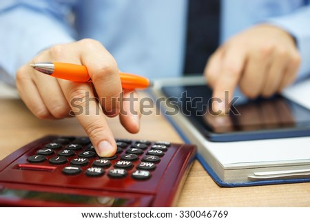financial analyst  is calculating return on investment with financial papers and on line data - stock photo
