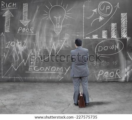 Financial analyst reading financial diagram on chalkboard - stock photo