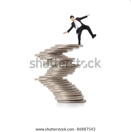 financial and crisis concept. businessman standing on the unstable coins - stock photo