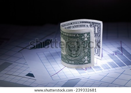 Financial background. Closeup of one dollar note standing on paper with chart - stock photo