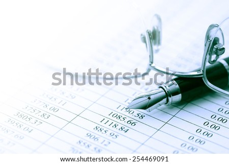 Financial background. Closeup of spectacles near pen on paper sheet with digits - stock photo