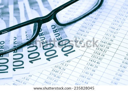 Financial background. European Union Currency near spectacles on paper background with digits table