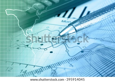Financial background in greens and blues with map, calculator, graph and pen. - stock photo
