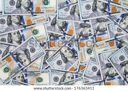 Financial background of American 100 dollar bills scattered randomly with the portrait of Benjamin Franklin uppermost, closeup view - stock photo