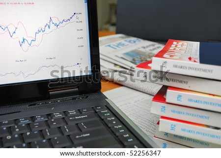 Financial books with laptop showing graphs and charts. Camera focus on graph. For concepts such as business and finance, internet and technology, and stock analysis and financial investment.