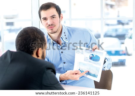 Financial business plans. Confident businessman holding a financial statistics and shows it to his colleague in the office of the table in the formal wear. - stock photo