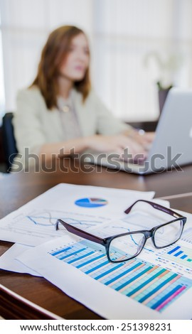 financial chart near dollars seen by unfocused glasses ( colleagues meeting to discuss their future financial plans only silhouettes being viewed )  silhouette of a girl working at the computer - stock photo