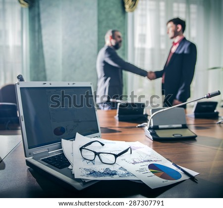 financial chart near dollars seen by unfocused glasses ( colleagues meeting to discuss their future financial plans only silhouettes being viewed ) two businessmen shake hands, dark blue colors - stock photo