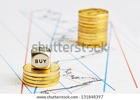 Financial chart, rising coins stacks, dices cube with the word BUY. Selective focus