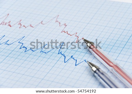Financial chart shows  a graph in two colors red and blue with two pens made on millimeter paper,selective focus - stock photo