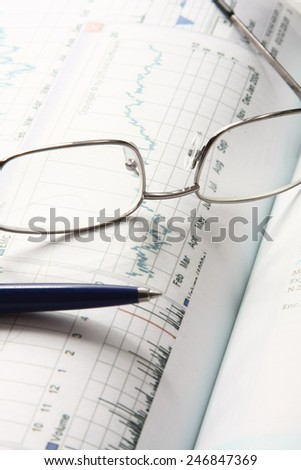 Financial charts, a pen and glasses - stock photo