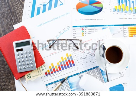 financial charts and graphs and a pen on the office table - stock photo