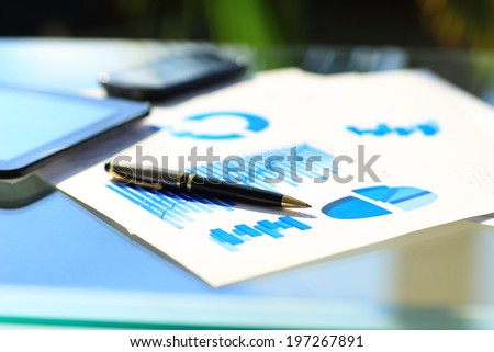 Financial charts on the table with tablet and pen - stock photo